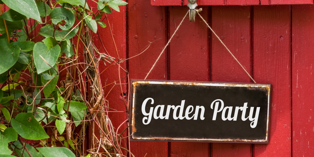 Garden party on a sign hanging from a red door