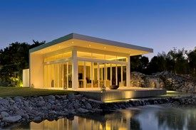 Illuminated summer house/pavilion by the lake at night with Origin's folding doors